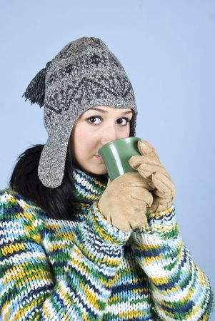 Portrait of beauty teen girl with cap,gloves and pullover standing and drinking hot drink to heat up over blue background photo