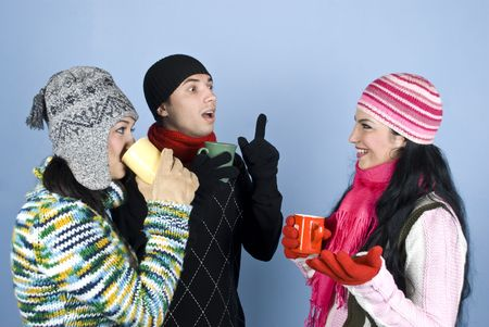 Three happy friends  in winter clothes with  sweaters,hats,scarves and gloves holding hot cup of tea  and drinking  ,laughing and having  a cheerful conversation,the guy explaining something and gesticulate  over blue background photo