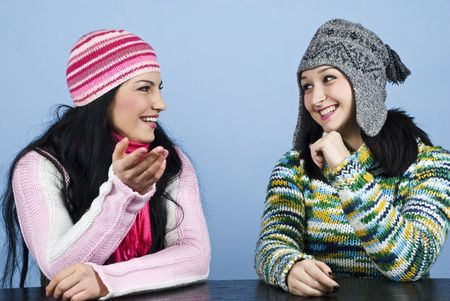 Two women friends  in winter clothes having an conversation and sitting at table,they laughing and gesturing  and looking each other over blue background photo