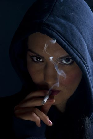 Bad girl in a hood smoking in darkness and looked provocative