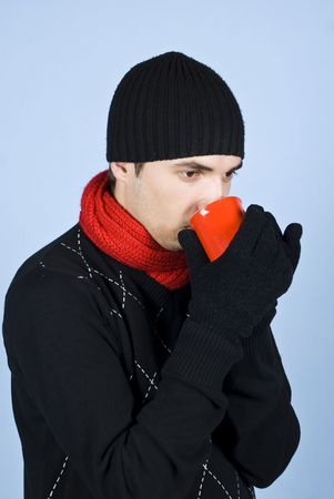 Young man standing in profile and drinking hot tea from a red mug,he wearing scarf,cap  gloves over blue background photo