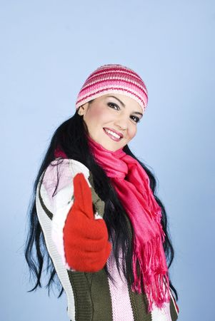 Happy brunette woman in winter clothes with cap,scarf,gloves giving thumbs up and smiling over blue background Stock Photo - 5997458