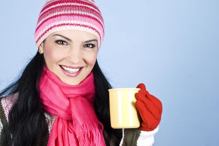 Portrait of happy smiling winter woman  holding a cup with hot drink and copy space for text message in right part of image over blue background photo