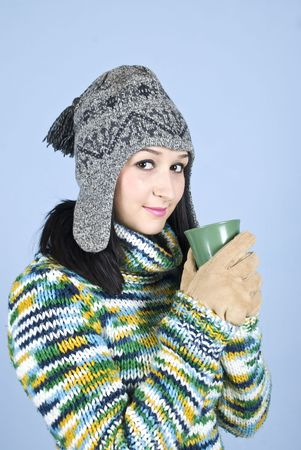 Beauty teen female holding a mug with hot drink and standing in semi profile looking at you over blue background photo