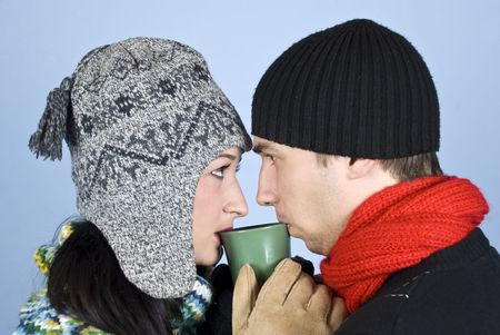 Couple of young people dressed in winter clothes with hats on heads,sweaters standing face to face and looked at each other drinking a hot drink from same mug photo