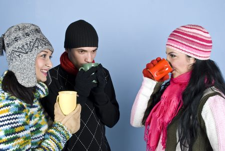 Group of young friends enjoying a hot drink and a conversation together ,they having a discussion,drinking  and smiling over blue background photo