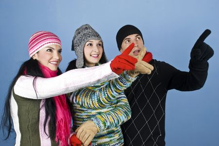 Cheerful  winter people friends having fun and all pointing up to something and looked happy and surprised  over blue background photo