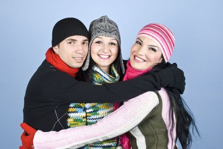 Happy group of people  friends dressed in winter clothes  standing embrace  and smiling together concept of united friendship over blue background photo