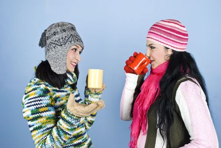 Two beautiful woman friends dressed in winter clothes enjoying a conversation,drinking hot drink and laughing together over blue background photo