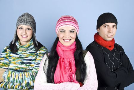 Cheerful friends in winter clothes standing together in a group with arms folded and smiling for you over blue background photo