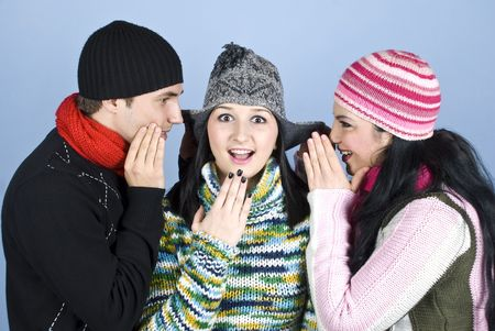 Happy friends  in winter season having fun,a young woman standing in middle and looked surprised  while her friends telling her a secret and raise the cap ears over blue background Stock Photo - 5997481