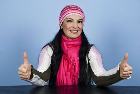 Beautiful woman in winter clothes sitting at table and giving thumbs up with both hands over blue background Stock Photo - 5997473