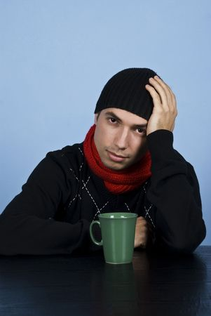 Sad winter man sitting at table with a hot drink and  being depressed and holding his hand on head over blue background photo