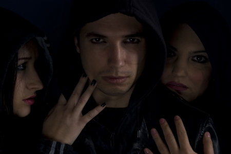 Gang guy member in the middle of two passionate  women with black hood ,concept of bad urban street boys photo