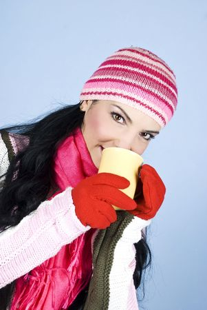 Beautiful brunette woman in pink winter clothes drinking a cup of hot drink and looking at you,right angle view photo