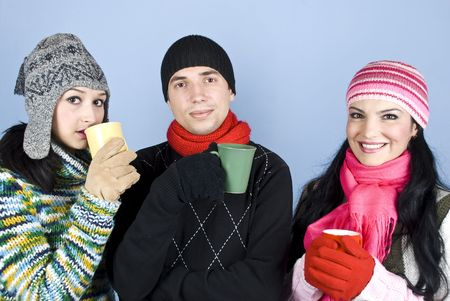 Friends in warm clothes with caps,pullovers and gloves enjoying a hot drink together and  smiling over blue background photo