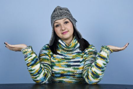 Worried young  female  dressed in winter clothes wonder what happens or answering i do not know  sitting at table with hands stretched over blue background