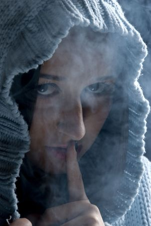 Head of young woman with hood wool in night with many smoke around her standing with finger at mouth like she say: sssst ,be quiet!Concept of nightlife harmful photo
