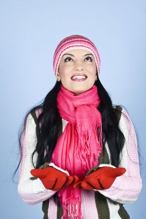 Beautiful brunette woman  dressed in winter clothes smiling ,looking up,standing with hands open and waiting for snow or something else  over blue background photo