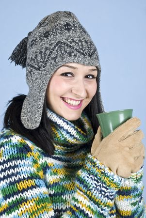 Happy laughing female teen in winter clothes  holding a hot drink  to heat up  over blue background photo
