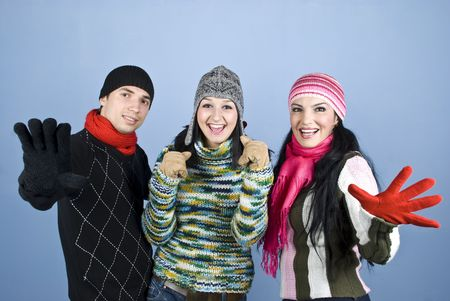 Happy smiling three friends showing happiness and excitement and standing with hands gloves in front of image over blue background photo