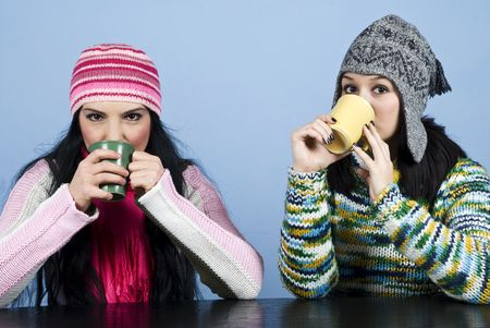 Two women dressed in winter clothes sitting at table and drinking a hot drink together  over blue background photo