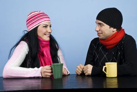pullovers: Young couple having a funny conversation and standing  face to face at table enjoying a cup of tea together  Stock Photo