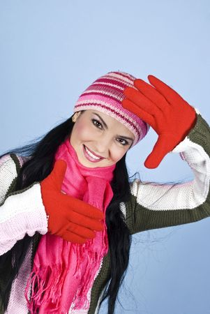 Happy young winter woman framing her face with hands in gloves and smiling,right angle view photo