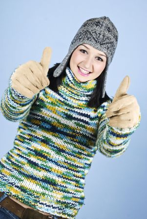 Successful girl in green sweater with cap giving thumbs up with both hands over blue background Stock Photo - 6026851