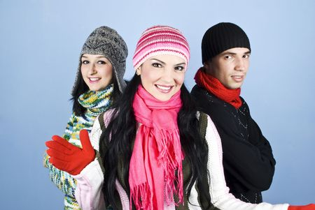 Smiling friends in winter  clothes standing together with a woman in middle who invite to join their group photo