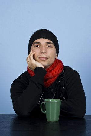 Young sad man  in winter clothes standing at table with hand to chin and thinking over blue background photo