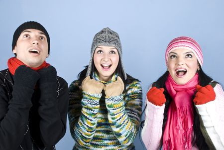 Happy three friends in winter clothes cheering and looking up surprised .You can add in that image gifts,presents,money,snowflakes falling  over their heads. photo