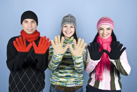 Happy friends in winter clothes standing in a line showing their palms in colorful gloves over blue background photo