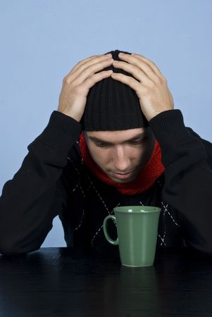 Depressed young man in black pullover and cap standing at table with hands on head and being worried photo