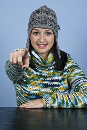 Youth female in winter clothes pointing to you and sitting at table over blue background photo
