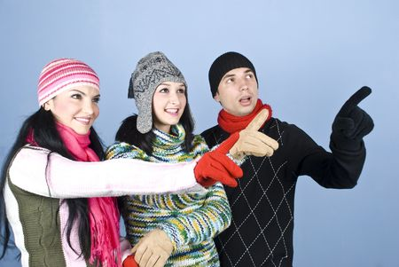 indicate: Happy three people friends in winter clothes indicate up with fingers and smiling and looking surprised