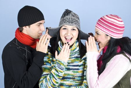 Three friends having fun,two of them trying to tell a secret to girl in middle at her cap ears and all laughing together photo