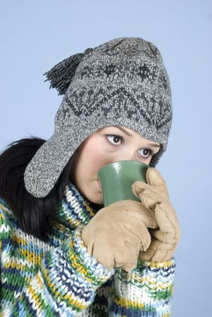 Girl in winter clothes drinking a hot drink in semi profile over blue background photo