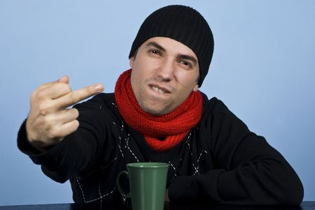 middle finger: Young man in winter clothes being very upset and showing obscene gesture