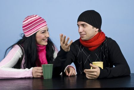 Young couple sitting at table and having a funny conversation,the man explaining something and gesturing and the woman laughing.They also enjoying a hot drink photo