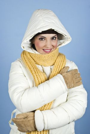 Woman in winter white jacket  with hood,scarf and gloves smiling for you over blue background photo