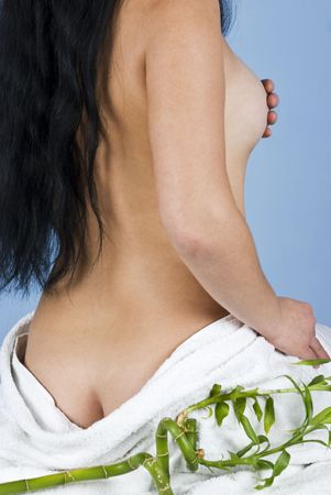 Back side of part of woman body at spa massage standing in semi  profile with hand covering  breast with a white towel around body and a bamboo photo