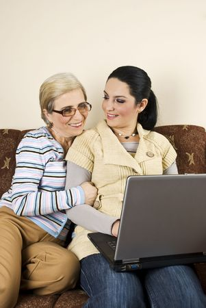 Two women sitting on sofa,using laptop and having a funny discussion and laughing together photo