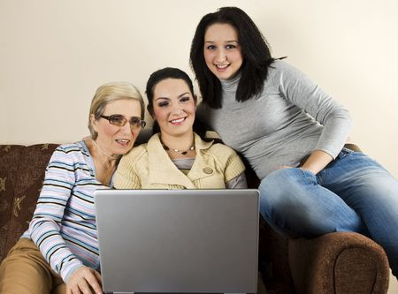Mother with two daughters sitting on laptop and having fun  using laptop,they smiling and having conversation together photo