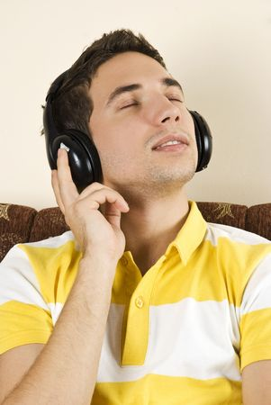 Young man sitting on couch in living room and listening music with eyes closed Stock Photo - 6091107