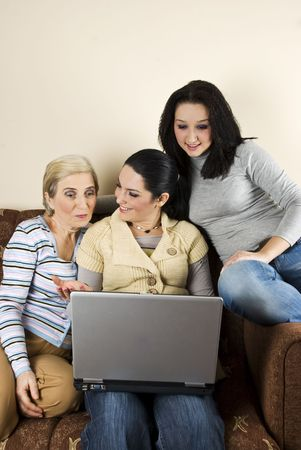 Mother and her daughters sitting on sofa in living room and having a conversation while using laptop,one of daughters explain her mom something and she is surprised but happy photo