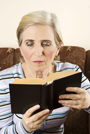 Beauty senior woman reading a book and sitting comfortable in her couch photo