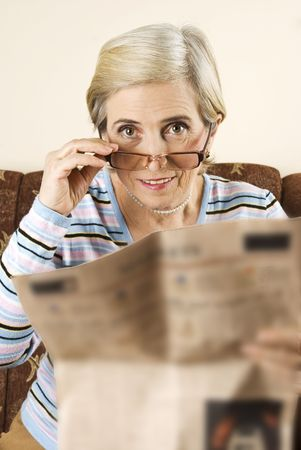 Senior woman put the eyeglasses and prepare for reading a newspaper photo