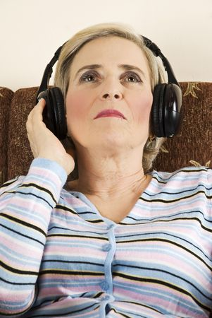 Beauty senior woman sitting on couch and listening music in headphones,she looking up and holding her hand to  headphone Stock Photo - 6102403