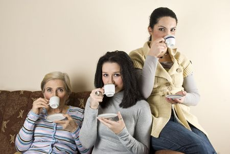 Three women friends enjoying a coffee and a conversation in living room,sitting all on sofa Stock Photo - 6102399